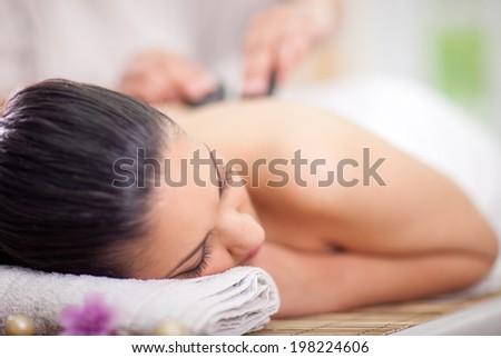 Beautiful woman having a wellness back massage at spa salon - stock photo