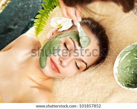 Beautiful woman having clay facial mask apply by beautician. - stock photo
