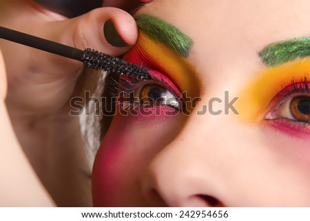 Beautiful Woman Having Colorful Makeup Put On Her Face - stock photo