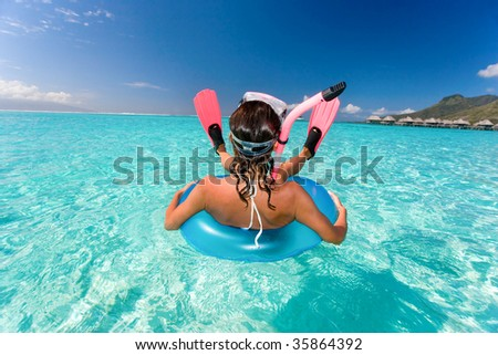 beautiful woman having fun floating in turquoise waters - stock photo
