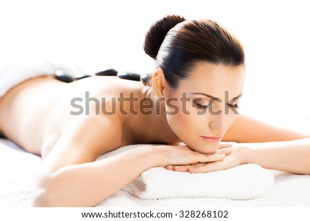 Beautiful woman having hot stones on her back in spa salon. - stock photo