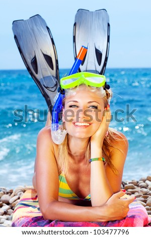 Beautiful woman having outdoor fun, female on the beach, happy teen girl wearing mask and fins, water sport, healthy young lady tanning and sunbathing, summer vacation, holidays travel - stock photo