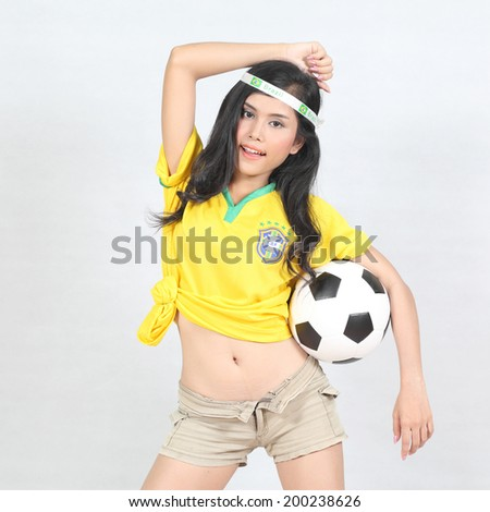 Beautiful woman hold ball with wearing Brazil football top