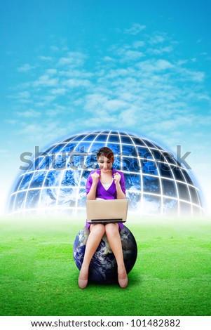 Beautiful woman hold notebook computer and digital world background on the grass field : Elements of this image furnished by NASA