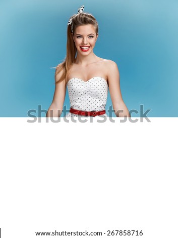 Beautiful woman holding a blank billboard on blue background  / photo set of young American pin-up model on blue background with space for text - stock photo