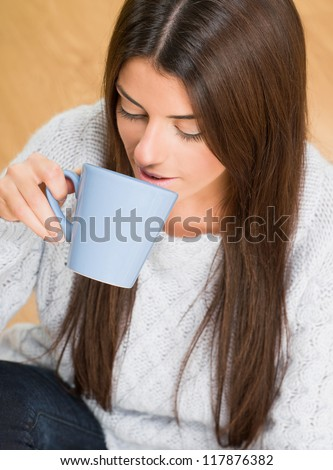 beautiful woman holding a blue mug while sitting on the floor