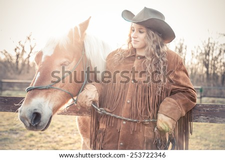 Beautiful woman holding a brown horse - Pretty caucasian model with stallion outdoors - stock photo