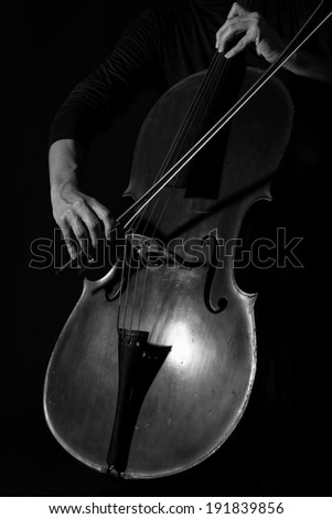 Beautiful woman holding a cello with selective light in black dress artistic conversion