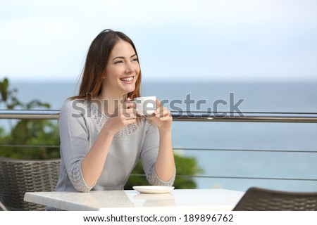Beautiful woman holding a cup of coffee in a restaurant with the sea in the background - stock photo