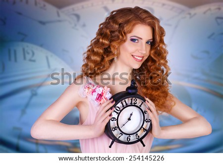 beautiful woman holding a large clock. beauty portrait of cheerful red-haired girl with long curly hair. against the background of hours - stock photo