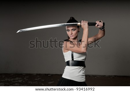 Beautiful woman holding a long shining steel ceremonial sword above her head with copyspace. - stock photo
