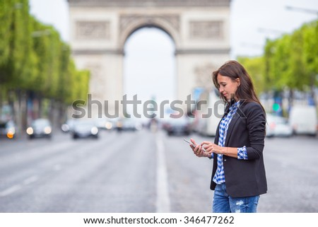 Beautiful woman holding a phone on the Champs Elysees in Paris - stock photo