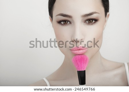 beautiful woman holding a powder brush near her face, studio white