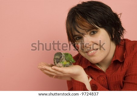 beautiful woman holding baby parrot - stock photo