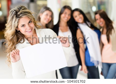 Beautiful woman holding banner with a group of girls behind - stock photo