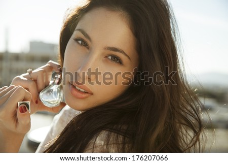 beautiful woman holding bottle of perfume and smelling aroma. horizontal shot - stock photo