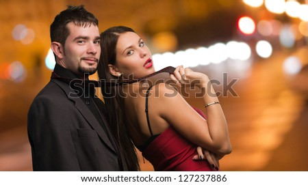 Beautiful Woman Holding Businessman Tie at a city by night - stock photo