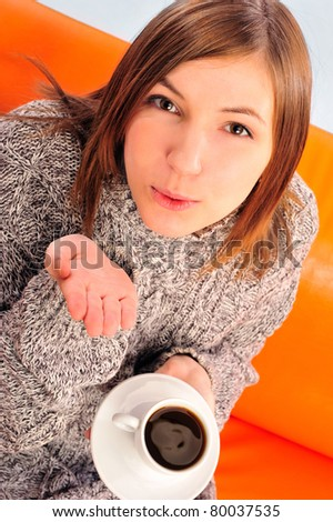 Beautiful woman holding cup of black coffee sitting on couch wearing warm sweater. Sending air kiss to camera