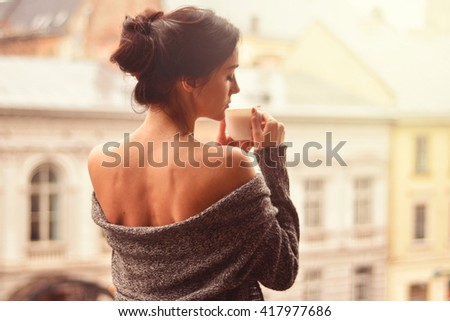 Beautiful woman holding cup of coffee standing on the balcony. Fascinated by the aroma of coffee - stock photo