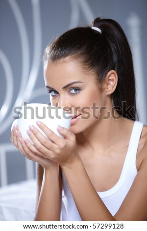 Beautiful woman holding cup on white bed - stock photo