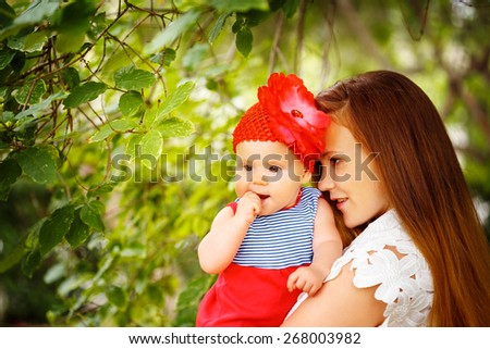 Beautiful woman holding cute curious Toddler Baby in red clothes. Relaxing in green summer Park. - stock photo