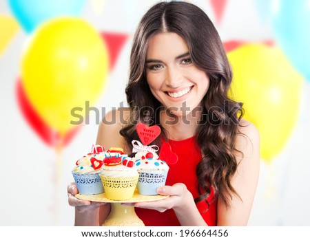 Beautiful woman holding cute party cupcakes - stock photo
