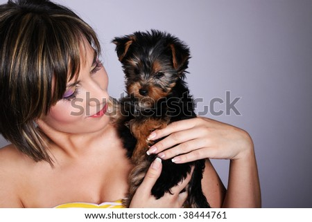 Beautiful woman holding dog on her arms