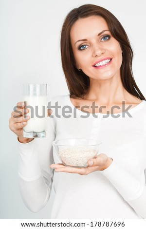 beautiful woman holding glass of mik and bowl with dry oatmeal flakes - stock photo