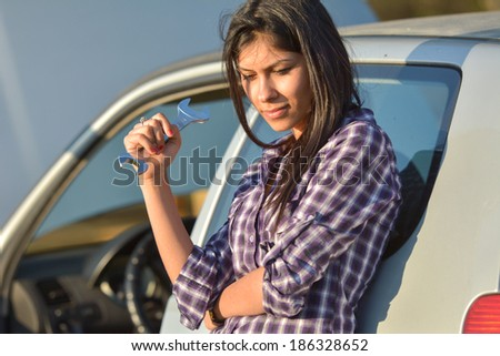 Beautiful woman holding Hand wrench near broken car  - stock photo