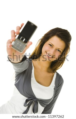 Beautiful woman holding in reach hand mobile phone. Looking at camera and smiling. Front view. White background. - stock photo