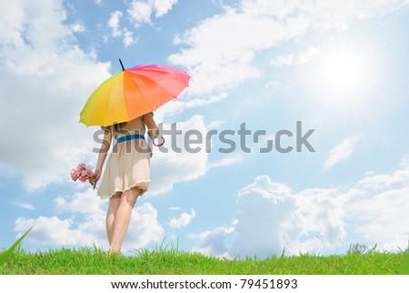 Beautiful woman holding multicolored umbrella and cloud sky - stock photo