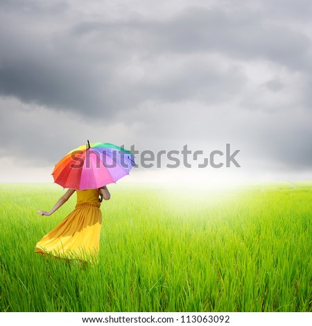 Beautiful woman holding multicolored umbrella in green rice field and rainclouds - stock photo
