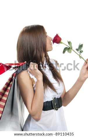 Beautiful woman holding red rose flower, shopping bags, presents in supermarket on a white background - stock photo