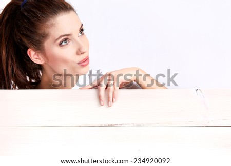 Beautiful woman holding sign. Image of woman standing behind wood board / placard. Beautiful caucasian model. - stock photo