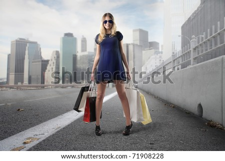Beautiful woman holding some shopping bags on a city street - stock photo