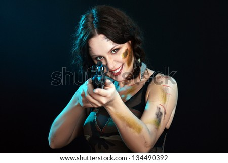 Beautiful woman holding weapon weared camo over dark background - stock photo