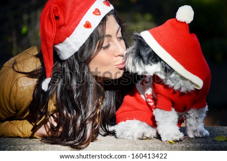 beautiful woman hugging her dog with red christmas hat - stock photo