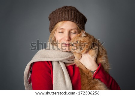 Beautiful woman hugging her red cat portrait on grey background. - stock photo
