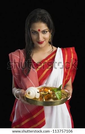 Beautiful woman in a Bengali sari holding pooja thali - stock photo