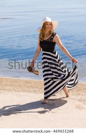 stock photo beautiful woman in a black and white sun dress walking along the beach 469651268