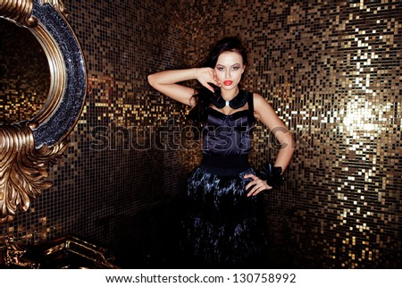 Beautiful woman in a black dress on a gold background mirror - stock photo
