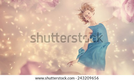 Beautiful woman in a blue dress in a pink peony flower fantasy