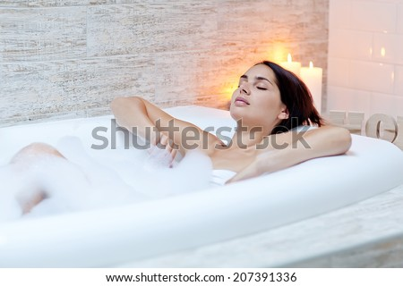 Beautiful woman in a bubble bath - stock photo
