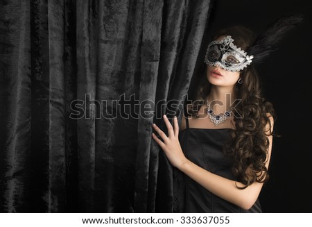 Awesome Beautiful Woman In A Carnival Mask Behind The Velvet Curtain On Dark  Background. Space For