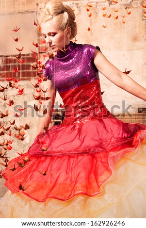 Beautiful woman in a formal dress with origami birds - stock photo