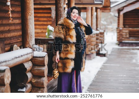 beautiful woman in a fur coat and scarf.  Russian village. Winter. - stock photo