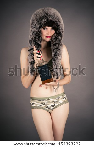 beautiful woman in a fur hat with a bottle of whiskey