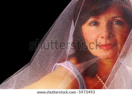 Beautiful woman in a gauzy veil, like a bride's - stock photo