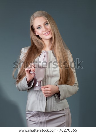 beautiful woman in a gray suit against a dark background in the office