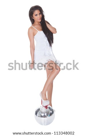 Beautiful woman in a party dress standing on a glittering mirrored silver disco ball in a nightlife and entertainment concept - stock photo